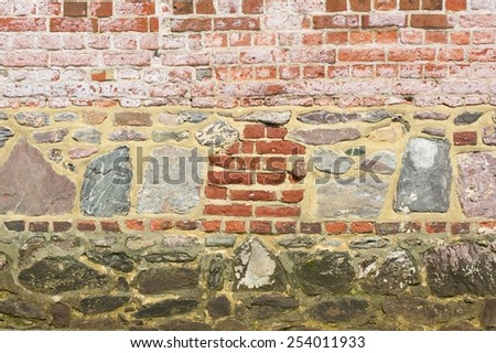Wall of mixed stone and brick at Bosham, West Sussex, England - stock photo