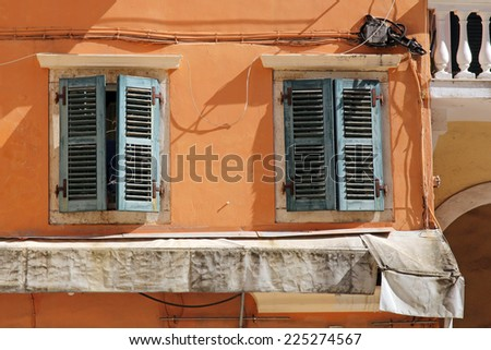 wall of traditional greek house with window with wooden shutters - stock photo
