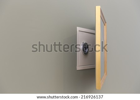 Wall safe hidden over painting with copy space - stock photo