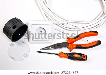 Wall socket, socket box, power cable and electrician tools on white background - stock photo