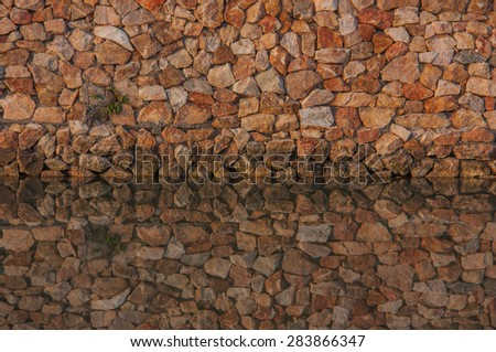 Wall stones and water reflection. - stock photo