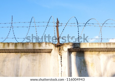 Wall with barbed wire on a background of blue sky - stock photo