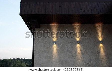 Wall with three lamps that shine up and down, outdoor. Selective focus. - stock photo