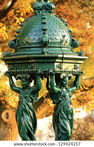 "Wallace fountain in Paris by fall / One of the drinking fountains in Paris so called ""Wallace fountains"" in autumn with yellow foliage as a background. - stock photo"
