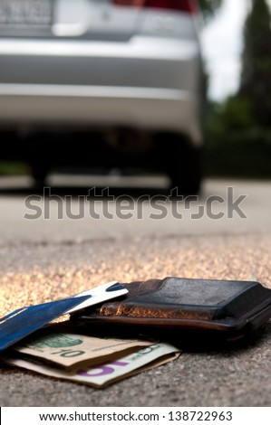 Wallet dropped on the ground behind a car, forgotten by owner - stock photo