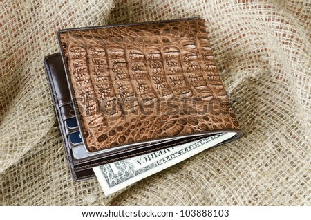 Wallet made of genuine crocodile leather over the linen background - stock photo