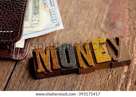 Wallet with American Money and the word Money in letterpress letters. - stock photo