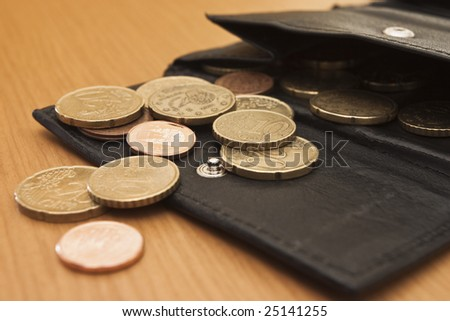 Wallet with some coins in it over a wooden table. - stock photo