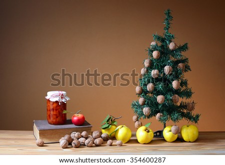 Wallnuts and quinces with a pine tree on a table - stock photo