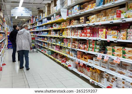 WALLONIA, BELGIUM - OCTOBER 17: Consumers shopping in the Cookies section. Aisle with a variety of packaged biscuits products in a Carrefour Hypermarket on October 17, 2014 in Wavre, Belgium - stock photo