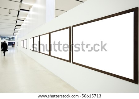 Walls in museum with empty frames and person move - stock photo