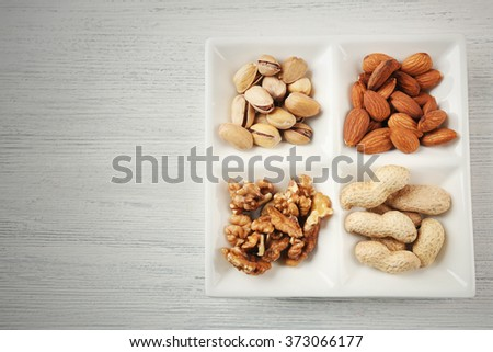 Walnut kernels, almonds, pistachios, peanuts in the ceramic rectangle plate on the wooden table - stock photo