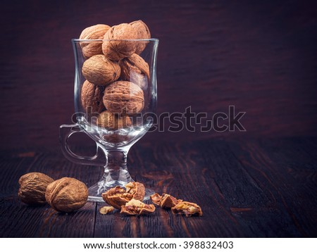 Walnut kernels and whole walnuts in a glass on a dark old wooden table - stock photo