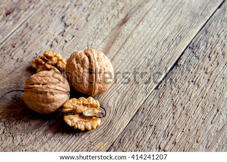 Walnut kernels and whole walnuts on rustic old wooden table with copy space - stock photo