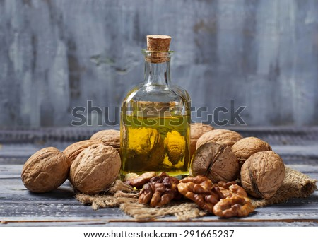 Walnut oil in bottle and nuts. Selective focus - stock photo