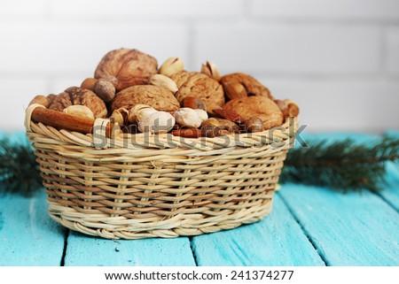 Walnuts, almonds, pistachios to a wicker basket - stock photo
