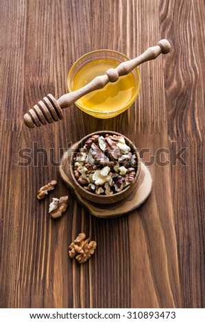 Walnuts and honey on a dark wooden table - stock photo