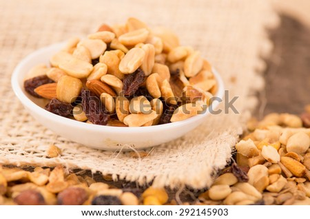 Walnuts and other nuts in a white bowl with raisins - stock photo