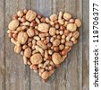 walnuts, hazelnuts and peanuts on wooden background/nuts/heart - stock photo