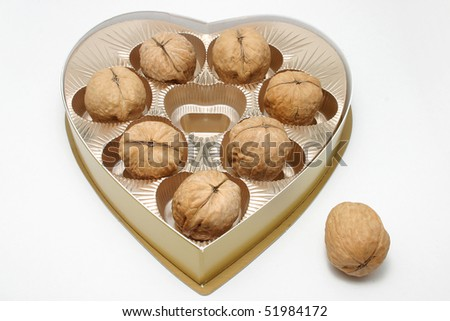 Walnuts in a golden heart shape chocolate box. - stock photo