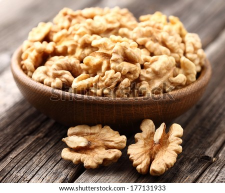 Walnuts in a wooden plate - stock photo