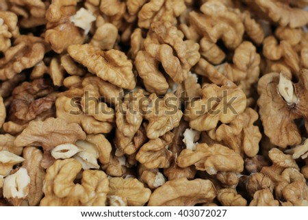 Walnuts in closeup. Walnut kernels and whole walnuts on rustic old wooden table - stock photo