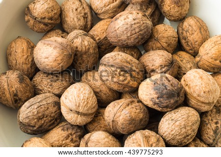 Walnuts in shell in a white bowl - stock photo