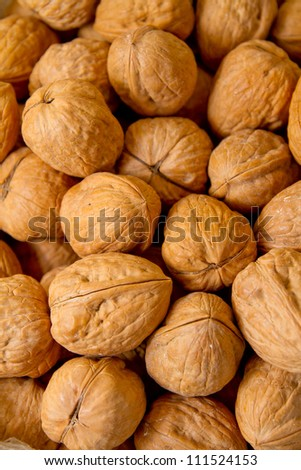 Walnuts in shells, one upon the other - stock photo