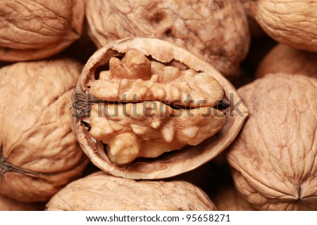 Walnuts in shells, one upon the other, one nut open - stock photo