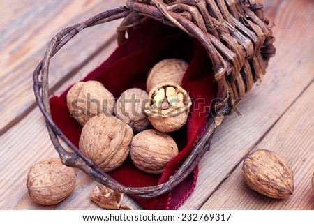 Walnuts in the vintage basket with red napkin. Russian tradition to eat nuts on Christmas holidays. Selective focus - stock photo