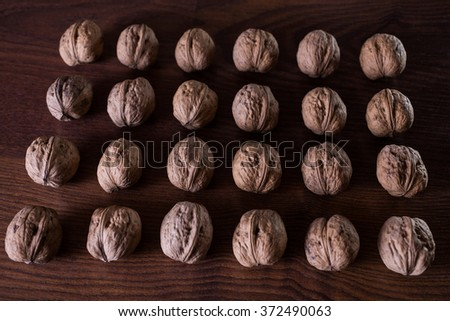 walnuts on a dark background, conceptual photography, walnuts lie in a row in a heap - stock photo