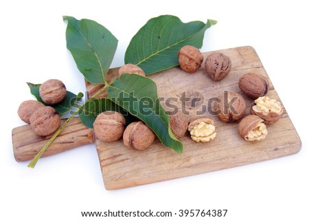 Walnuts on green leaves and wooden board - isolated on white                          - stock photo