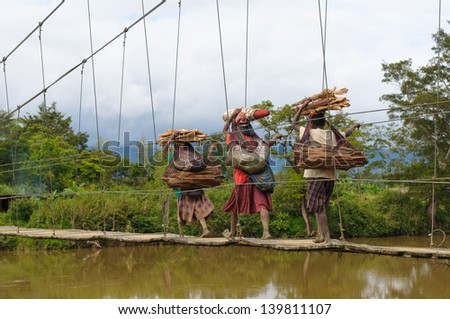 WAMENA, PAPUA, INDONESIA - NOV, 14: Papuan women crossing bridge on November, 14, 2008 near Wamena, Papua, Indonesia. - stock photo