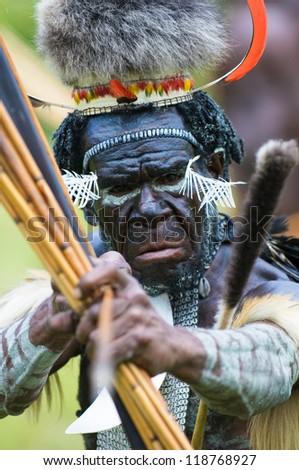 WAMENA, PAPUA, INDONESIA - NOVEMBER 14: Yali Mabel, the chief of Dani tribe performing traditional fighting dance on November, 14, 2008 near Wamena, Papua, Indonesia. - stock photo