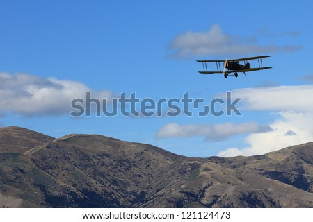 """WANAKA MARCH 03: Bristol F.2B vintage aircraft flies over the mountains during the royal New Zealand air force 75th anniversary""""Warbirds Over Wanaka"""" airshow on March 03, 2012 in Wanaka New Zealand - stock photo"""
