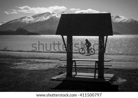 WANAKA, NEW ZEALAND - September 22: A tourist cycles past a bench on the Lake Wanaka waterfront  on September 22 2015 in Wanaka, New Zealand.  Wanaka is a popular tourist destination. - stock photo