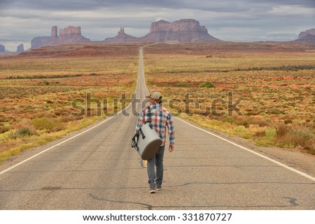 Wanderer or loner in Monument Valley walking down an empty road - stock photo