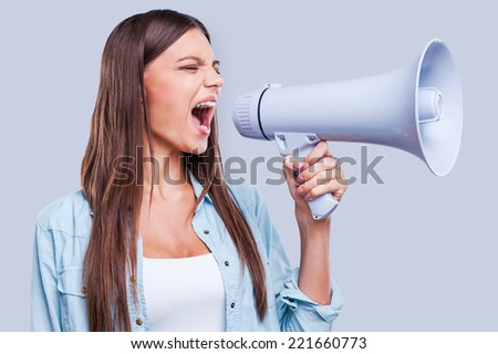 Want to be heard. Attractive young woman shouting through a megaphone, holding it in her hand while standing against grey background - stock photo