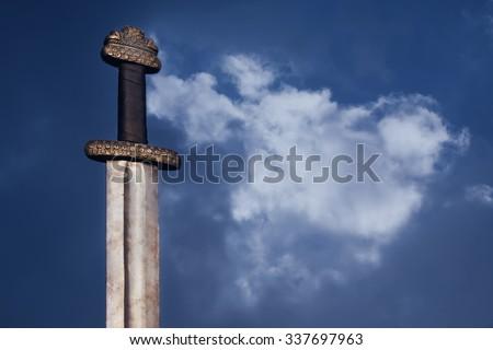 War symbol. Medieval viking sword against a dramatic sky - stock photo