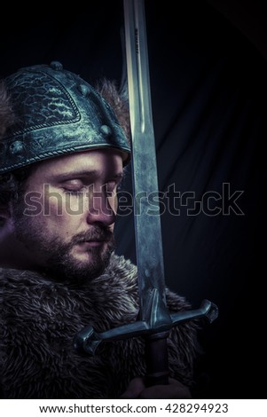 War, Viking warrior with iron sword and helmet with horns - stock photo