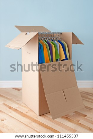 Wardrobe box filled with colorful clothing, prepared for transportation. - stock photo
