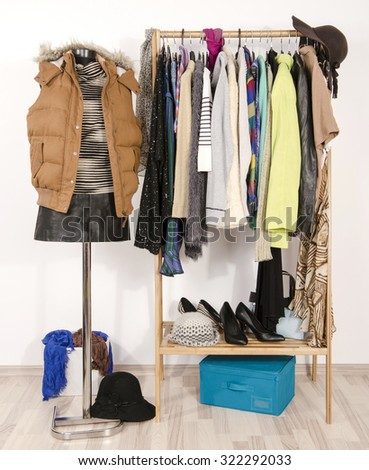 Wardrobe with clothes arranged on hangers and a winter outfit on a mannequin. Dressing closet with autumn clothes and accessories. Tailor's dummy wearing a winter vest with leather skirt. - stock photo
