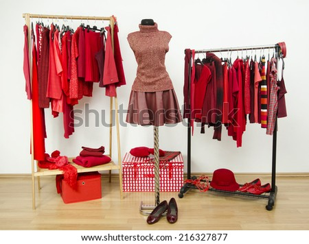 Wardrobe with red clothes arranged on hangers and an outfit on a mannequin. Dressing closet full of all shades of red clothes, shoes and accessories. - stock photo