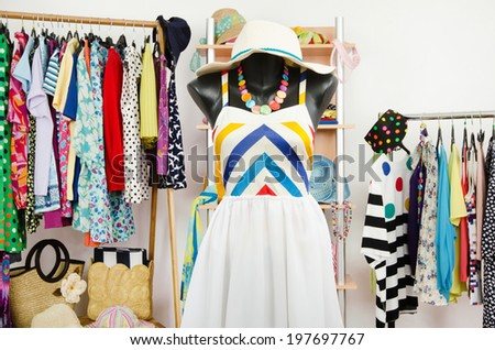 Wardrobe with summer clothes nicely arranged and a beach outfit on a mannequin. Dressing closet with colorful clothes and accessories on hangers and a shelf. - stock photo