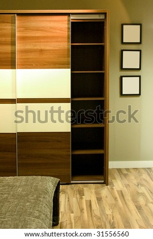 Wardrobe with three photo frames on the wall. - stock photo