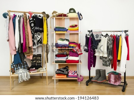 Wardrobe with winter clothes nicely arranged. Dressing closet with colorful clothes and accessories on hangers and a shelf. - stock photo