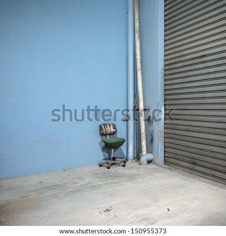 Warehouse interior corner with broken office chair held together with gaffer tape. - stock photo