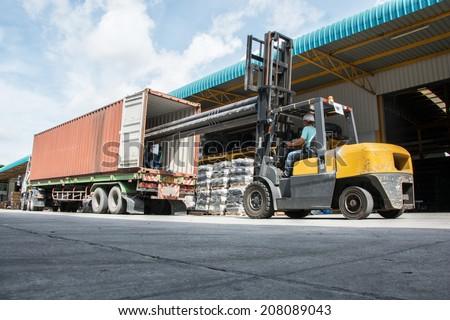 warehouse laborer team at unloading works with forklift loader - stock photo