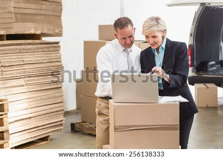 Warehouse manager and colleague using laptop - stock photo
