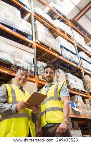 Warehouse manager and foreman looking at camera in a large warehouse - stock photo